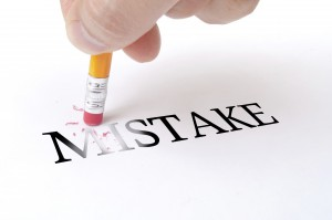 "Male hand holding wooden pencil and deletes the word ""MISTAKE"" on the white paper"