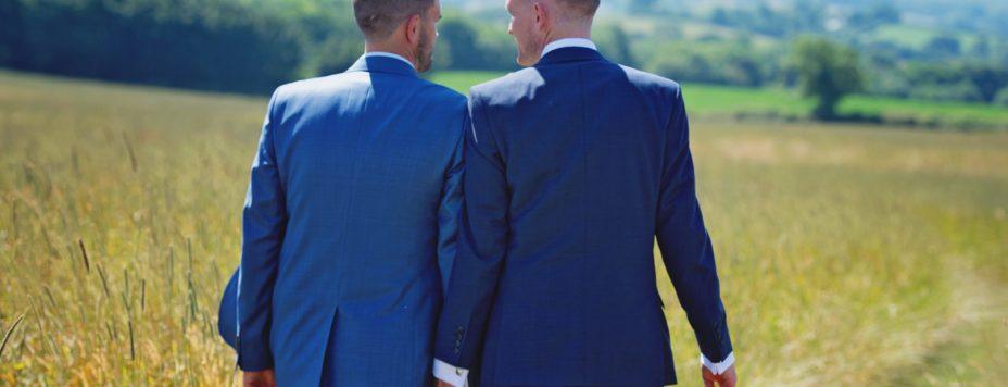 Homosexualität und Islam: Zwei Männer in Anzügen, die über ein Feld an einem sonnigen Tag spazieren, während sie Händchen halten